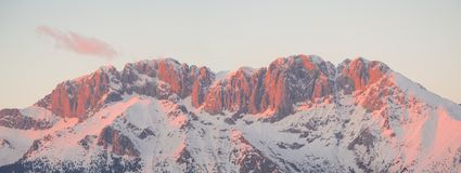 Presolana is a mountain range of the Orobie, Italian Alps. Landscape in winter. At sunset the rocks become red, orange and pink. Presolana is a mountain range of royalty free stock photography