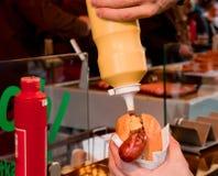 Pressão de mão alguma mostarda em um cachorro quente com uma salsicha alemão em um guardanapo de papel Fotos de Stock