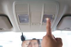 Pressão de mão dos homens a luz de teto do carro foto de stock