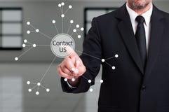 A pressão do homem de negócio contacta-nos botão em s transparente digital Fotografia de Stock