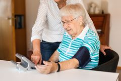 Pressão sanguínea de medição da mulher superior em casa com ajuda da outra mulher fotografia de stock royalty free