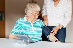 Pressão sanguínea de medição da mulher superior em casa com ajuda da outra mulher foto de stock royalty free