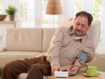 Pressão sanguínea de medição do ancião em casa fotos de stock royalty free