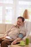 Pressão sanguínea de medição do ancião em casa Foto de Stock Royalty Free