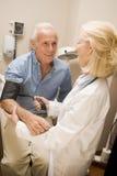 Pressão sanguínea do doutor Checking do homem fotografia de stock royalty free
