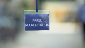 Press accreditation pass against blurred background, media ID card during event. Stock footage stock footage
