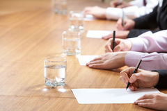 Press conference. Row of writing hands on table Stock Image