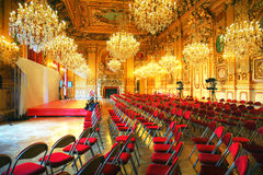 Press conference in antique ballroom. Preparing a press conference in an antique castle ballroom with crystal chandelier, gold paintings and red velvet chairs Stock Images