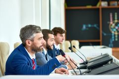 Press Conference at Full Speed. Profile view of confident entrepreneurs wearing elegant suits sitting in row at table and answering questions from audience Stock Image