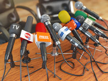 Press conference or interview concept. Microphones of different mass media, radio, tv and press prepared for conference meeting. 3d illustration Royalty Free Stock Images