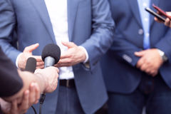 Press conference. Media interview. Reporters making interview with businessman, politician or spokesman. News conference Royalty Free Stock Photos