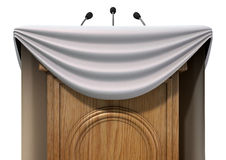 Press Conference Podium With Draping. A wooden speech podium with three small microphones attached and decorated with generic white draping on an isolated white Stock Photos