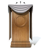 Press Conference Podium With Draping. A wooden speech podium with three small microphones attached and decorated with generic white draping on an isolated white Stock Images