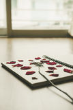 Press dried rose flower in note book page, on wood texture, vintage tone Royalty Free Stock Photography