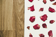 Press dried rose flower with petals, on white paper and wood floor, vintage tone Stock Image