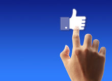 Press Facebook Like Button. Hand pressing Facebook Like Button on blue background royalty free stock image