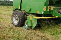 Press machine form round fresh hay straw bale roll Royalty Free Stock Photos