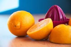 Press med citroner som ligger på en trätabell Royaltyfri Foto