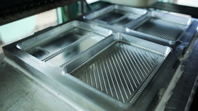Press molds for production of plastic containers for food storage. Goods manufactured of plastic packaging. Work on high performance machinery inside of plant stock footage