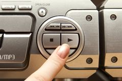 Press play button on audio system.  Stock Image