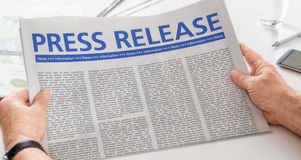 Press Release. Man reading newspaper with the headline Press Release Stock Photo
