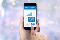 Press Release. Person holding a smartphone on blurred cityscape background Stock Photos