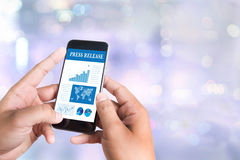 Press Release. Person holding a smartphone on blurred cityscape background Royalty Free Stock Image