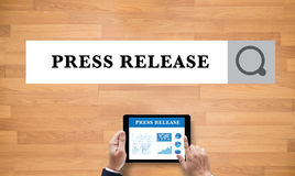 Press Release. On the tablet pc screen held by businessman hands - online, top view Royalty Free Stock Photos