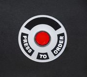 PRESS TO ORDER FAST FOOD BUTTON ON BLACK BACKGROUND. A red center button beckons the customer to press to order food royalty free stock image