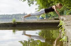 Press ups. Woman doing press ups by water Stock Image