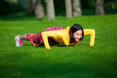 Press ups exercise by young woman. Girl working Royalty Free Stock Photo