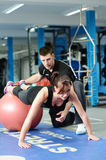Press ups on gym ball with personal trainer Stock Photos