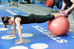 Press ups on gym ball with personal trainer Stock Image