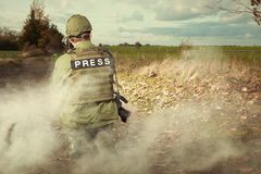 Press in war - journalist in field. Photographer in war conflict field zone observing royalty free stock images