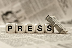 Press. Woodn dice depicting the letters PRESS with a bundle of small newspapers leaning on the right dice Stock Photography