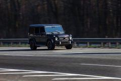Pressa preta de G Wagen do Benz de Mercedes na estrada vazia Foto de Stock