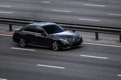 Pressa preta do Benz E de Mercedes na estrada vazia Imagens de Stock Royalty Free