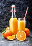 Pressade nytt orange fruktsaft i glasflaska arkivbilder