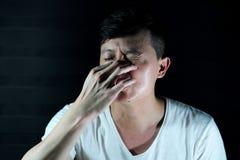 Pressar den asiatiska mannen för ståenden hans näsa vid hans finger royaltyfria bilder