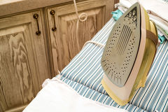 Pressboard and iron. Close-up of process ironing clothes on press board Royalty Free Stock Photography