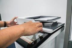 Presse d'homme d'affaires sur l'imprimante de bureau pour les documents de copie et de balayage image stock