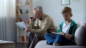 Presse de lecture de grand-papa, garçon à l'aide du comprimé, générations et progrès technologique photos stock