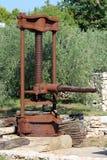 Presse forte rouillée d'huile d'olive de cru en métal montée en machine sur la base concrète utilisée comme décoration de jardin  images libres de droits