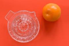 Presse-fruits en verre avec une orange d'isolement sur un fond orange photo stock