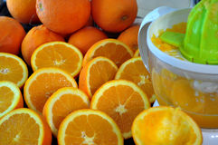 Presse-fruits et beaucoup demi oranges Images stock