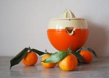 Presse-fruits orange et blanc avec quelques petites oranges sur une table de marbre photographie stock