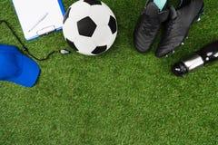 Presse-papiers avec du ballon de football et bottes sur l'herbe Images stock
