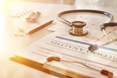 Presse-papiers avec l'électrocardiogramme et le traitement avec la lumière d'or Image libre de droits