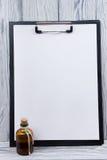 Presse-papiers avec la page blanche du papier et de la bouteille sur le fond en bois Copiez l'espace Image stock