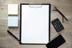 Presse-papiers avec le smartphone et la calculatrice de page blanche sur le fond en bois Photos libres de droits